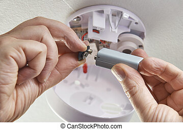 Close Up Of Replacing Battery In Domestic Smoke Alarm