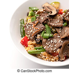 Close up of Rice with meat and sesame seeds. Food plate isolated on white background, Top view. Appetizer dish from restaraunt menu. Exquisite served dish. Soft focus