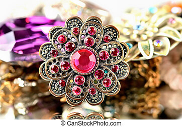 Close-up of richly decorated brooch - red artificial stones