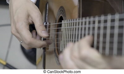Close up of right hand playing guitar
