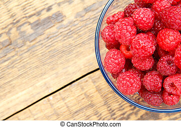 Close up of ripe raspberries in the glass bowl on wooden boards
