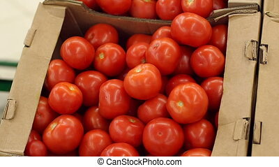 Close-up of ripe red tomatoes in a box on the counter in the supermarket.