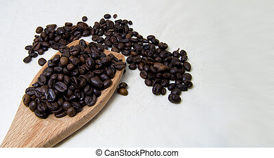 close up of roasted coffee beans on a wood spoon with white background with space for text.