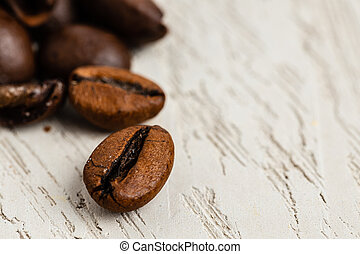 Close up of roasted coffee beans on wooden surface