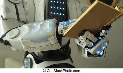 Close up of robotic machine reading book