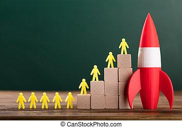 Rocket Besides Yellow Human Figures On Top Of Wooden Blocks