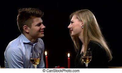 Close up of romantic dinner table with kissing young couple in bkack background.