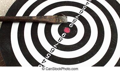 Close up of rotating dart board with broken arrow