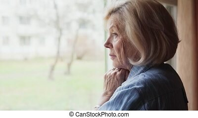 sad old woman turning her head and looking into the camera