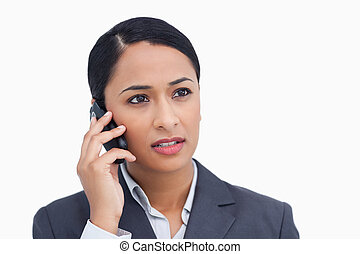 Close up of saleswoman listening to caller against a white...