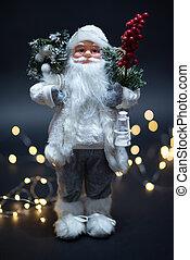 Close up of Santa Claus toy portrait shot against magical golden lights