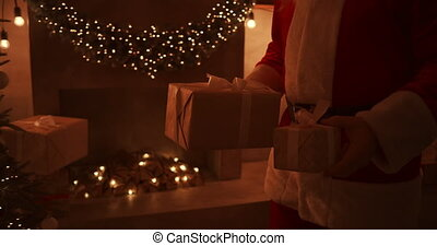 Close - up of Santas hand: brings gifts under the Christmas tree for children. Give gifts to children on Christmas night. Santa puts a gift under the Christmas tree. High quality 4k footage