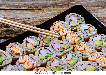 close up of sashimi sushi set with chopsticks and soy - sushi roll with salmon and sushi roll with smoked eel,