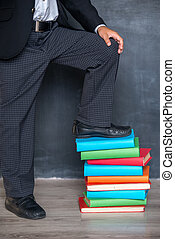 Close-up of school boy standing on books
