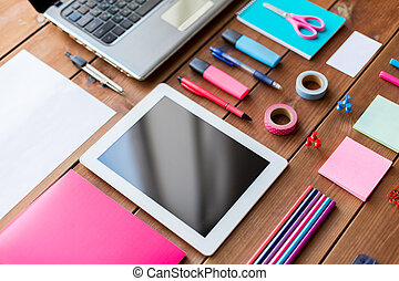 close up of school supplies and tablet pc