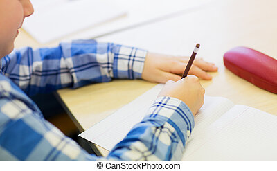 close up of schoolboy writing test at school - education, ...