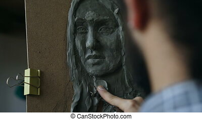 Close-up of Sculptor creating sculpture of human's face on...