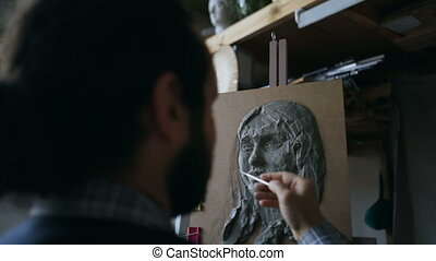 Close-up of Sculptor creating sculpture of woman's face on...