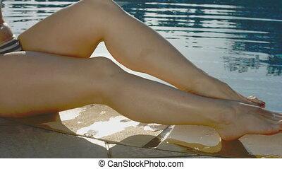 Close-up of seductive female legs near the pool, woman flirting