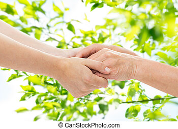 close up of senior and young woman holding hands - age, care...