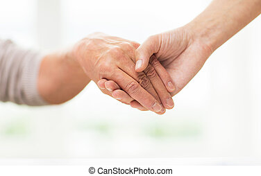 close up of senior and young woman holding hands - people,...