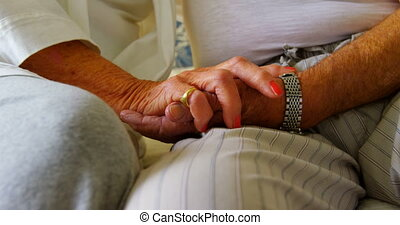 Close-up of senior couple holding hands in bedroom at comfortable home 4k