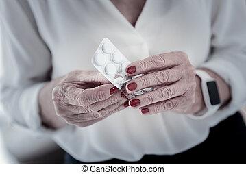 Close up of senior hands that holding medicine