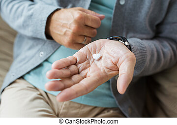 close up of senior man hand with heart shaped pill