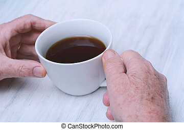 Close up of senior man holding cup of coffee