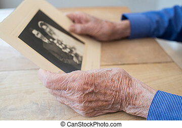 Close Up Of Senior Man Holding Wedding Photograph