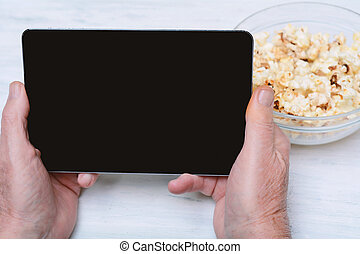 Close-up of senior man watching movie on tablet with popcorn