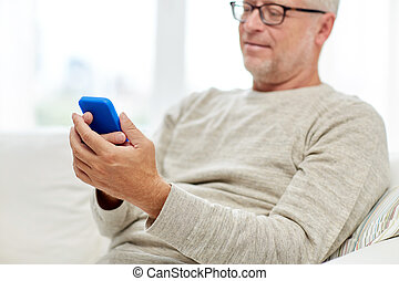 close up of senior man with smartphone at home