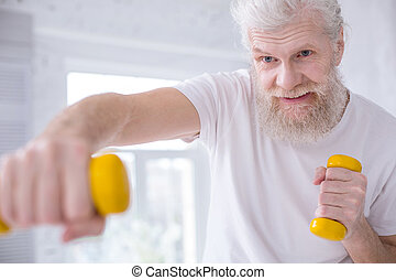 Close up of senior man working out with dumbbells