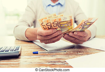 close up of senior woman counting money at home