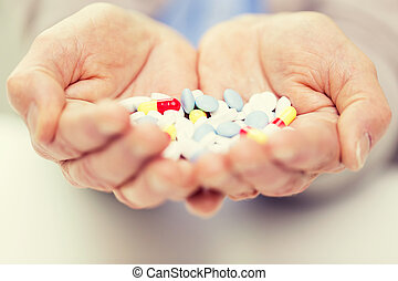 close up of senior woman hands with pills
