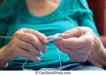 Close Up Of Senior Woman Sitting In Chair At Home And Knitting