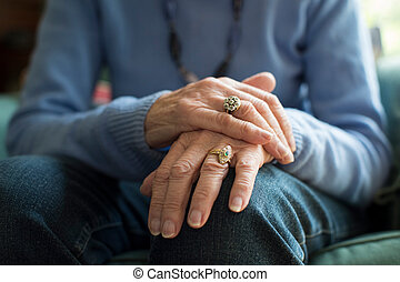 Close Up Of Senior Woman Suffering With Parkinsons Diesease