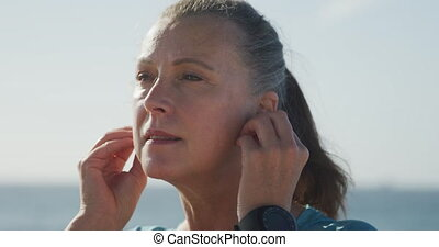 Close up of senior woman using wireless earphones - Senior ...