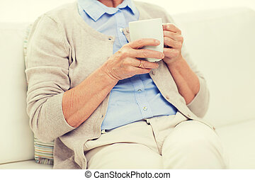 close up of senior woman with tea  cup at home