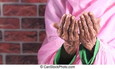 Close up of senior women hand praying at ramadan .