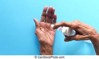 close up of senior women hand using sanitizer gel for preventing virus .