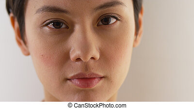 Close up of serious Asian woman's face