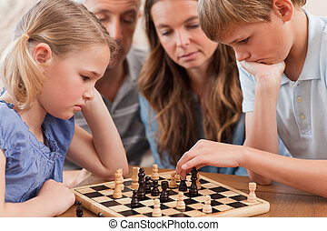 Close up of serious children playing chess in front of their...