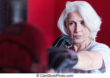 Close up of serious elderly woman boxing