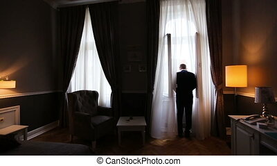 Close up of serious young fiance dressing up and looking at window on his wedding day .