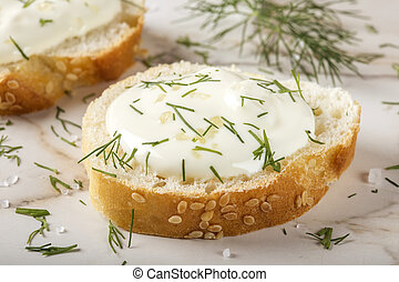 Close up of sesame bagel with cream cheese and dill on table