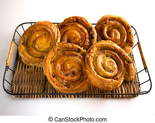 French raisin pastries on a wicker trail and white background