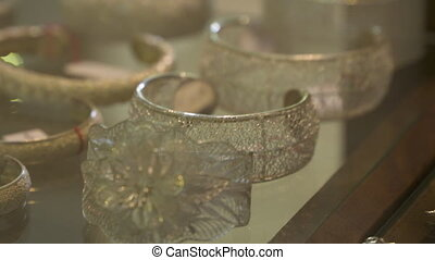 Tilting shot showing several silver bracelets made of patterns of thin wire
