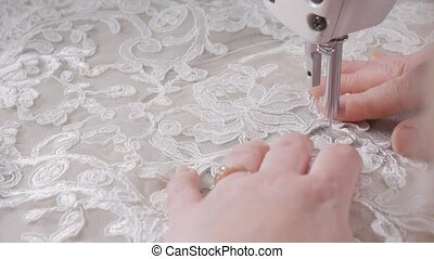 close-up of sewing machine, stitch thread seam. Equipment for sewing elegant wedding dress. Hand made