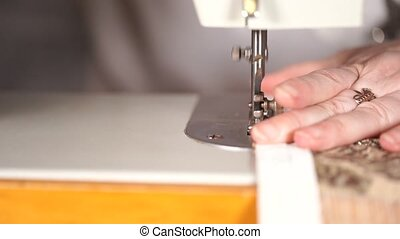 Close up of sewing machine with women's hands on table. Woman stitching curtain, using sewing machine